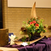 """2015 eerste Advent: De engel komt voor in het verhaal van Zacharias, wat verteld wordt bij de kinderen. Advent is er om ons voor te bereiden op de geboorte van Jezus De kleur is paars. De 12 bloemen staan voor het getal van Gods volk, er waren 12 stammen. (Jes. 60 :1-11). De rode kleur van de bloemen verwijst naar de Heilige Geest. Het """"puur feest"""" dat vandaag in de dienst gevierd wordt, wordt straks gevierd in het Koninkrijk van God. Ook al is het soms donker om ons heen, de glorie van de Heer zal van ons afstralen, omdat de Heilige Geest in ons is. (Openbaring 21:12 – 22:5). De hemel raakt de aarde in de belofte van een kind. Ongeloof, verstening, worden tot hoop en vertrouwen, daar waar de hemel de aarde raakt."""