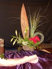 2015 derde Advent: Deze 3e advent is de kleur roze; midden in deze donkere dagen breekt het licht door. De hemel raakt de aarde, daar waar mensen elkaar ontmoeten. Maria en Elisabeth mogen elkaar tot steun zijn, samen delen zij het nog geheime geschenk. De boog in deze schikking maakt de verbinding tussen Maria en Elisabeth zichtbaar. De gesloten witte lelie in knop als beeld van verwachting. De rode Gerbera's verbeelden de Heilige Geest. (Lucas 1: 39-56)
