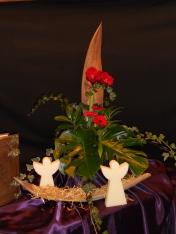 Kerstnacht 2015: God zal eens regeren over zijn volmaakte koninkrijk. Er zal vrede zijn en er zullen zegeningen zijn. De hemel raakt de aarde. De 3 gerbera's staan voor de drie-enige-God. God draagt ons en houdt ons in zijn hand , de vingerbladeren staan daar symbool voor.(micha 4) Het stro; symbool voor Jezus in de kribbe. Wij mogen net als de engelen God Loven , prijzen en eren.