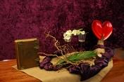 2016 Derde Lijdenszondag: Jezus is liefde. Liefde is ….... Welkom, Jezus, Gods Zoon, Die als een nederige Koning, reed op een ezel, wilde geen kroon, koos geen paleis tot Zijn woning. De palm tak verwijst naar dit gedicht en het verhaal van de kindernevendienst. Jezus volgt Zijn Vader en wij volgen Jezus. Het paarse pad door het bloemstuk. Wij moeten niet heersen, maar dienen. Uw stem bracht mij tot staan. Op deze heilig plek; Gods huis is een plaats om te bidden. Vandaar dat de bloemen horizontaal liggen. Wij staan even stil Liefde is …....Jezus volgen. N.a.v. Lucas 19: 29-44 en Mattheus 20:17-28 en 21: 10-27.