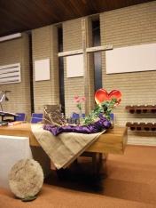 2016 Goede Vrijdag: Het kruis met prikkeldraad. Na het doven van de paarskaars is daar een roos tussen het prikkeldraad; het Licht lijkt te doven, maar de Liefde van God dooft nooit. Aan de voet van het kruis staan rode anemonen, zij zijn de tranen van Jezus. God zal een nieuwe hemel bouwen van Zijn liefde om jouw tranen heen. Nav Statie foto's van verhalen in glas in lood uit Oirschot.