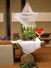 2016 Paasmorgen: Jezus is Liefde. Liefde is....... Heb je ze gezien vanmorgen, de narcissen, de violieren en de zijde wind lelies? ze stralen als de zon. Heb je het gehoord; de narcissen trompetteren het goede nieuws; De Heer is waarlijk opgestaan. Sta op, Gods nieuwe dag is aan gebroken! De 5 vijfvingerige bladeren om het bloemstuk heen, symboliseren dat God ons vast houdt maar ook draagt, altijd! De klimop bij de weg gerolde steen, benadrukt Gods trouw. Liefde is …......vertel het maar van de op gestane Heer.