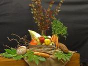 Oogstdienst 2016: Het koren is, wat er na het maaien is blijven liggen in het verhaal. De broden die van het graan zijn gemaakt. De handvormige bladeren onder de schikking verbeelden enerzijds de vele handen die ondanks machines voor de oogst nodig zijn en anderzijds het ontvangen van het leven door de oogst. Wij beelden onze dankbaarheid uit met groenten van de aarde. De rode takken verwijzen naar de liefde die we ontvangen. Lied 716 zegt het zo: Zaaien, maaien, oogsten. Dank de Allerhoogste! Voor zijn zorg om ons bestaan, Hij biedt ons dit alles aan. Dank de Allerhoogste! Voor zegen die Hij geeft. Zoals elk het leven heeft. Zaaien, maaien, oogsten. Dank de Allerhoogste! Nav Ruth 2.