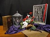 Tweede Advent 2016; Beloofd is beloofd.Langs de stammen zien we een rood koord waarmee Rachab de verspieders helpt om te ontsnappen. Het is een koord van hoop voor haar en haar familie. De boomstammen staan voor die hoop op en de verwachting van nieuw leven. Haar daad, haar geloof zal vruchten afwerpen in de heilsgeschiedenis van het godsvolk. Daarom zijn er druiven verwerkt in de schikking. De rode rozen en witte orchideeën verwijzen naar haar daadkracht. De klimop staat voor hoop en leven. Groot is uw trouw Heer. Nav. Jozua 2; Rachab.