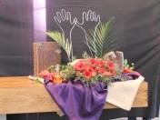2015 Zesde Lijdenszondag: We zien de slinger van rode bloemen die samen een weg vormen. Ze verwijzen naar de jassen die door de mensen uitgetrokken werden om een rode loper voor Jezus te vormen toen Hij de stad Jeruzalem binnentrok op een ezelsveulen. De handen juichen mee met de vele stemmen.