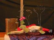 """2015 Goede Vrijdag: Op goede vrijdag gedenken wij hoe mensenhanden Jezus kruisigden, hoe mensen handen tot op vandaag mensen """"kruisigen"""" (de spijkers). Een hand wordt gebald vanwege de gebalde vuisten die naar Jezus werden opgestoken. De andere is open om de overgave van Jezus te symboliseren. De rode anemonen verwijzen naar het lijden van Jezus."""
