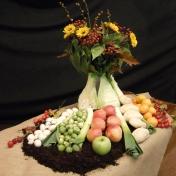 """2015 Oogstdienst: """"De aarde geeft voldoende, maar krijgt ieder zijn deel? Daarom zijn de groente en fruit in parten neergelegd, zodat ieder even veel ontvangt. Uit de aarde komt alle leven voort. De groente, het fruit, de bessen en het brood beelden de oogst uit. De zonnebloemen staan voor de dankliederen die we zingen . God heeft ons op vele manieren rijk gemaakt, nu mogen wij aan andere geven. Looft Hem die u met deze gave heeft verzadigd. (nav Schriftlezing: 2 Korintiërs 9;1-14)."""