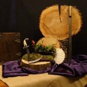 """Vierde Lijdenszondag 2017: We gebruiken een schijf van een boomstam als klok waarin we de jaarringen zien. Zij verraden de tijd die verstreken is, en verbeelden het thema bij de kindernevendienst: Het beslissende moment. Paars is de kleur van inkeer en past bij de 40 dagen tijd. Het mos staat voor stilte en de jute drukt de eenvoud uit in het stuk. """"Is geloven in Jezus meer dan genoeg?"""" De matzes staan voor Jezus die zegt: Ik ben het brood dat leven geeft (vers 35). Jezus wordt gearresteerd door een gewapende bende met zwaarden en messen. De christusdoorn als symbool voor het lijden dat Jezus te wachten staat. Dank u Jezus voor het offer van uw leven. Groot is uw trouw o Heer. N.a.v. Marcus 14 en Johannes 6."""