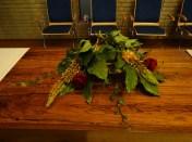 Pasen 2017: We gebruiken een schijf van een boomstam waarin we bloemen zien staan. Zij verraden de tijd die verstreken is, en verbeelden het thema: Een nieuwe tijd is aangebroken. Jezus is opgestaan, een nieuwe tijd breekt aan, het stralend licht overwint. Ook voor de belijdenis catechisanten breekt er een nieuwe tijd aan. Voor Lianne en Mariska elk een schikking met een groot blad en een rode en oranje bloem. Grote bladeren roepen het beeld op van gedragen worden. De klimop erbij als beeld van trouw en verbondenheid. De rode roos verbeeld de Heilige Geest die met hen mee gaat. Het groen als teken van overwinning. De kleur wit en geel op de liturgische tafel, voor feest: Het is paasfeest vandaag ! Al wat ten dode was gedoemd Christus onze Heer verrees. Dan zul je juichen om de Heer. Jezus is ons licht en leven N.a.v. Marcus 16 en Jesaja 41.