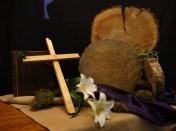 Zesde lijdenszondag 2017 : We gebruiken een schijf van een boomstam waarin we de jaarringen zien. Zij verraden de tijd die verstreken is, en verbeelden het thema bij de kindernevendienst: De tijd staat stil. Jezus wordt gekruisigd en roept luid: Mijn God, Mijn God, waarom hebt u mij verlaten? Het paarse kleed staat voor het linnen kleed waar Jezus in gewikkeld werd, waarna hij in het graf werd gelegd. Een ronde steen als symbool voor het graf. Daarvoor een liggend kruis waarop een lelie ligt, als teken van Jezus onschuld. Je hoeft niet bang te zijn. Gij zijt de rots waarop ik bouw. Ik heb U lief, o schoonste licht, glans van Gods aangezicht. nav; Marcus 15: 22-47
