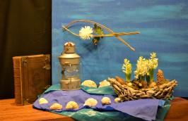 2de advent Begrijp je God liefde? Gods liefde brengt redding. Jona is Gods profeet. Hij moet de boodschap van God aan mensen overbrengen. God vertelt hem dat hij naar Nineve moet. De boot met hyacinten beeld dat uit. Jona wordt op een wonderlijke manier gered uit zee. Drie dagen verblijft hij in de vis. Jona is de chrysant in de vis. Tijd om na te denken, om de realiteit tot zich door te laten dringen dat hij verloren is. De enige die nog iets kan doen is God: de HEER die redt (vers 10), dan brengt God hem op het strand. Deze drie dagen kun je vergelijken met advent. De wereld was reddeloos verloren in de zonde en de gevolgen daarvan. Het symbool van de vis staat enerzijds voor de vis waarmee Jona werd gered; teken van redding. Maar ook als teken van het uitdragen van je geloof zoals de eerste christenen dat deden met het Ichthus-teken (=vis). Alleen God, de godslamp, kan de liefdeloosheid doorbreken door zijn Zoon te sturen en redding te brengen. Zijn wij ons ervan bewust dat Gods liefde geen luxe is, maar bittere noodzaak? En richten we ons, net als Jona, tot Hem in onze gebeden om genade en verlossing? N.a.v. Jona 1 en 2.