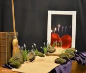 3e lijdenszondag 2018: Een open deur; speciaal voor Hem. Er branden 3 kaarsen op deze 3e zondag in de Veertigdagentijd. De schikking verwijst naar een gedeelte van het Evangelie van Johannes, waar Jezus de Tempel schoonveegt. Hij haalt de bezem door alle gesjacher en geldmakerij en maakt ruimte voor waar het werkelijk om gaat: onvoorwaardelijke liefde, een open huis zijn, de weg zoeken die naar het leven leidt. In de schikking is de weg 'schoongeveegd' en geven de blauwe druifjes de richting aan om door de deur te gaan. Jezus wil ons helpen om voor Hem ruimte te maken. De 'bloemen' zijn een teken van de vreugde die dat geeft in je leven. De nieuwe schepping is niet alleen een geschenk van Jezus, maar ook een opdracht aan ons. Jezus wilde dat de tempel een eerbiedige gebedsplaats was. Zo moet ook ons hart, waarin Gods Geest woont, een heilige plek zijn. Wie Jezus wil volgen, leeft voor Hem, naar Gods geboden. Het hart, de binnenruimte is een eerbiedwaardige plaats waar God vreugde tot bloei wil brengen. N.a.v.; Johannes 2: 13-25.