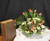 Wezenzondag 2018 Dit bloemstuk is deels gebruikt met Hemelvaart. De zondag tussen Hemelvaart en Pinksteren heet wezen zondag. De 11 tulpen staan symbool voor de 11 discipelen. De tulpen staan voor het gebed dat vandaag bij de lezingen centraal staat. De rood gekleurde bloemen zijn toegevoegd aan het bloemstuk, als voorafbeelding van het vuur van Pinksteren; de Geest komt er aan! N.a.v.: Psalm 84 en Johannes 17.