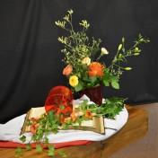 """Pinksteren 2018: Wij hebben de Pinkstervlammen verbeeld in dit bloemstuk, en hopen dat het u ook inspireert. Inspiratie betekent: Goddelijke ingeving. Wij zingen: """"Hoor Heilige geest, wij roepen u. Wees aanwezig in het woord."""" De bijbel ligt open, ontvang en hoor zijn woord en de Heilige Geest zal u levenwekkende kracht geven. Zoals Sifra ook de doop ontvangt en een kind van God is. De rode vazen en het geel, oranje boeket verbeelden de vuurtongen van de Heilige Geest. De klimop als beeld van trouw en verbondenheid. Geest van hier boven, leer ons geloven en ....... beziel ons! Geïnspireerd door Genesis 1, Psalm 87 en Handelingen 2."""