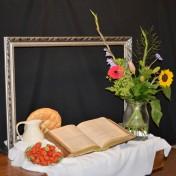 U kijkt naar een stilleven met de titel: 'Het beste gesprek met God.'Met daarin een kleurrijk boeket dat symbool staat voor de veelkleurige gemeente. De gladiolen verbeelden het groeiend vertrouwen dat nodig is voor een gesprek. Een goed gesprek wordt meestal gevoerd tijdens een maaltijd. Het brood en de wijn staan daar symbool voor. De aardbeien verbeelden de perfecte vriendschap onder elkaar en met God. De bijbel hebben we nodig om het beste gesprek met God te kunnen voeren! N.a.v. Hebreeën 13:2 en Genesis 18.