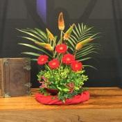 Pinksteren 2019: 'Pasen en Pinksteren op één dag.' De Geest verbindt: De klimop is altijd groen, hecht zich en staat symbool voor trouw. De Geest vlamt; De vuurpijlen (kniphofia) en gloriosa's verbeelden de vurige tongen die zich verspreidden en zich op ieder van ons neerzetten. De Geest bezielt: De liturgische kleur rood roept vuur en bezieling op, met hart en ziel geraakt worden. De Geest stroomt: Zo vraag God jou vandaag om open te staan voor steeds weer nieuwe vervulling met Gods heilige Geest. Ontvang de heilige Geest! Hij is de adem in jouw leven. Laat je vandaag door Hem leiden en vernieuwen. Na.v. Ezechiël 37 en Genesis 1.